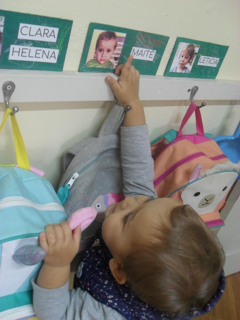 Criança apontando para o seu nome na parede