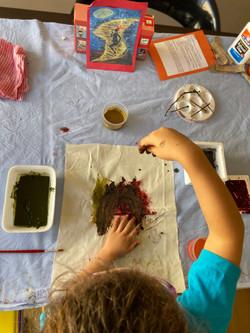 Menino pintando em tecido usando barro