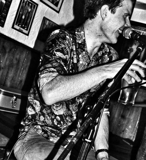 Liam Ward harmonica player smiling with microphone and pint glass