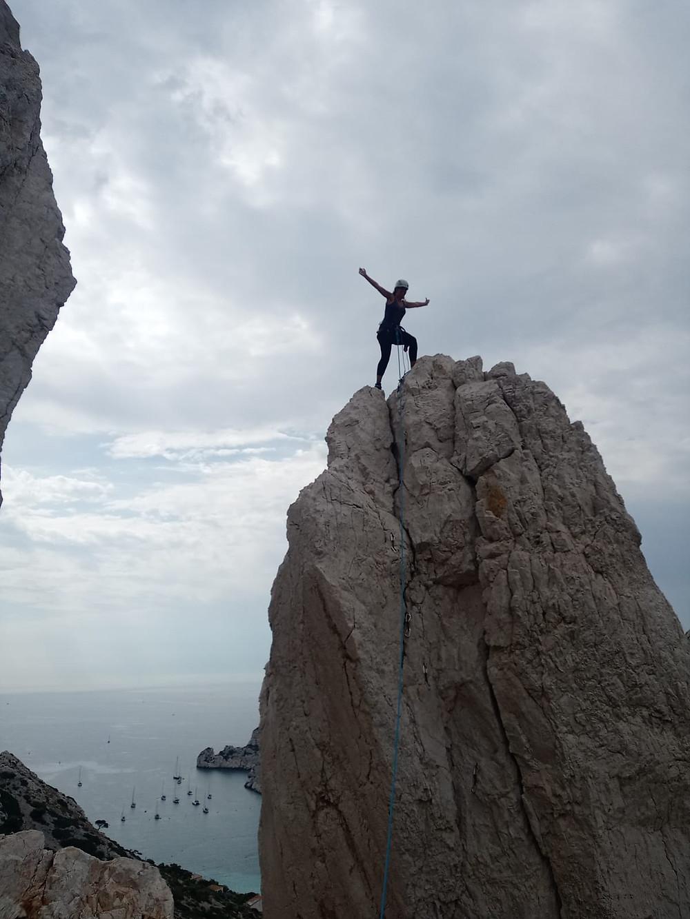 Une grimpeuse heureuse debout sur le pouce face à la mer