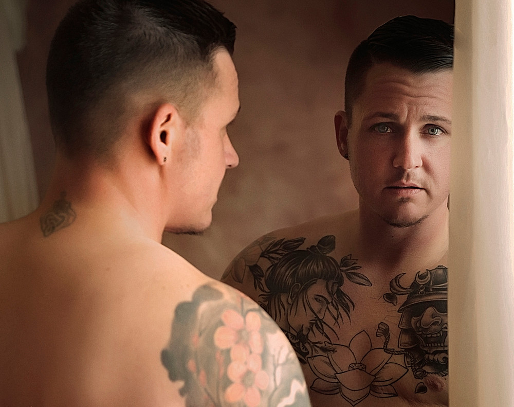 Tattooed man with blue eyes looking into a mirror in a male boudoir photo shoot