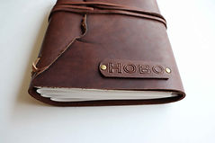 Close up of stamped initials on personalized brown leather journal.