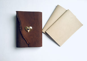 Brown leather refillable journal with gold heart decorative closure. Eco-friendly paper refill booklets sit beside.