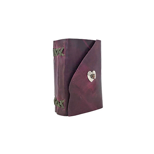 Main image of small purple leather journal. Natural edge of leather used on front closure flap. Silver heart shaped closure.