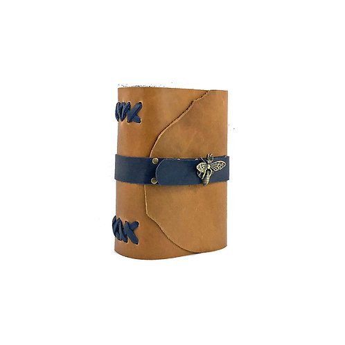 Main image of small tan leather journal with blue hand-stitched binding and brass bee closure.