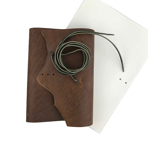 brown leather journal making kit. pre-cut leather journal cover and green leather ties with hole punched mixed media paper