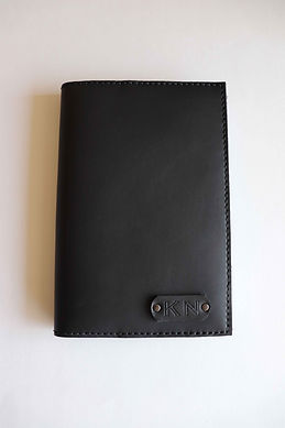 Handstitched black leather notebook cover personalized with stamped initials.