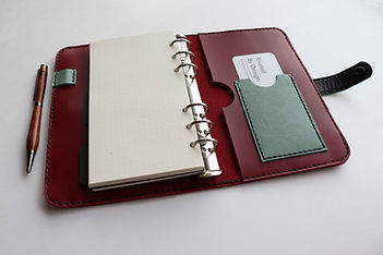 Red leather refillable personal planner with turquoise accent card pocket and pen loop.