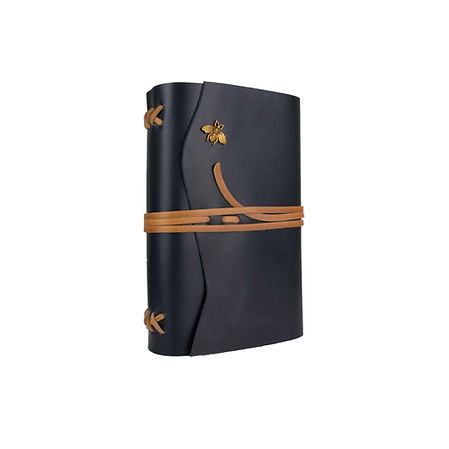 A dark blue leather journal with tan leather binding and closure ties and an antique gold bee embellishment.