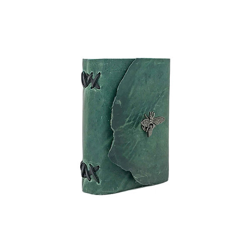Main image of small hand-bound green leather journal with black accents. Unique black bee closure.