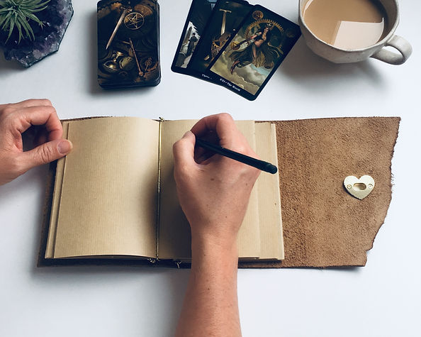 Hands writing in a brown leather refillable journal. Tarot cards and a cup of coffee are adjacent to the journal.