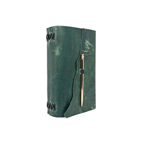 Main image of green leather journal hand-bound with black accents. Rose gold toned pineapple pen closure.