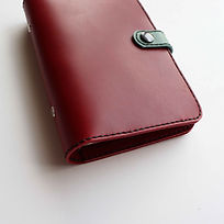 Close up of handstitched red leather personal planner.