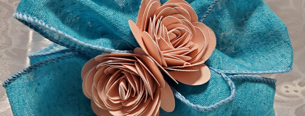 blue fabric bow with pink paper flowers