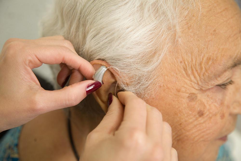Idoso com perda auditiva usando próteses auditivas
