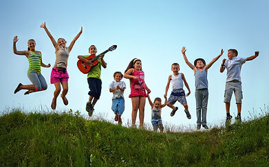 happy kids jumping on summer field.jpg