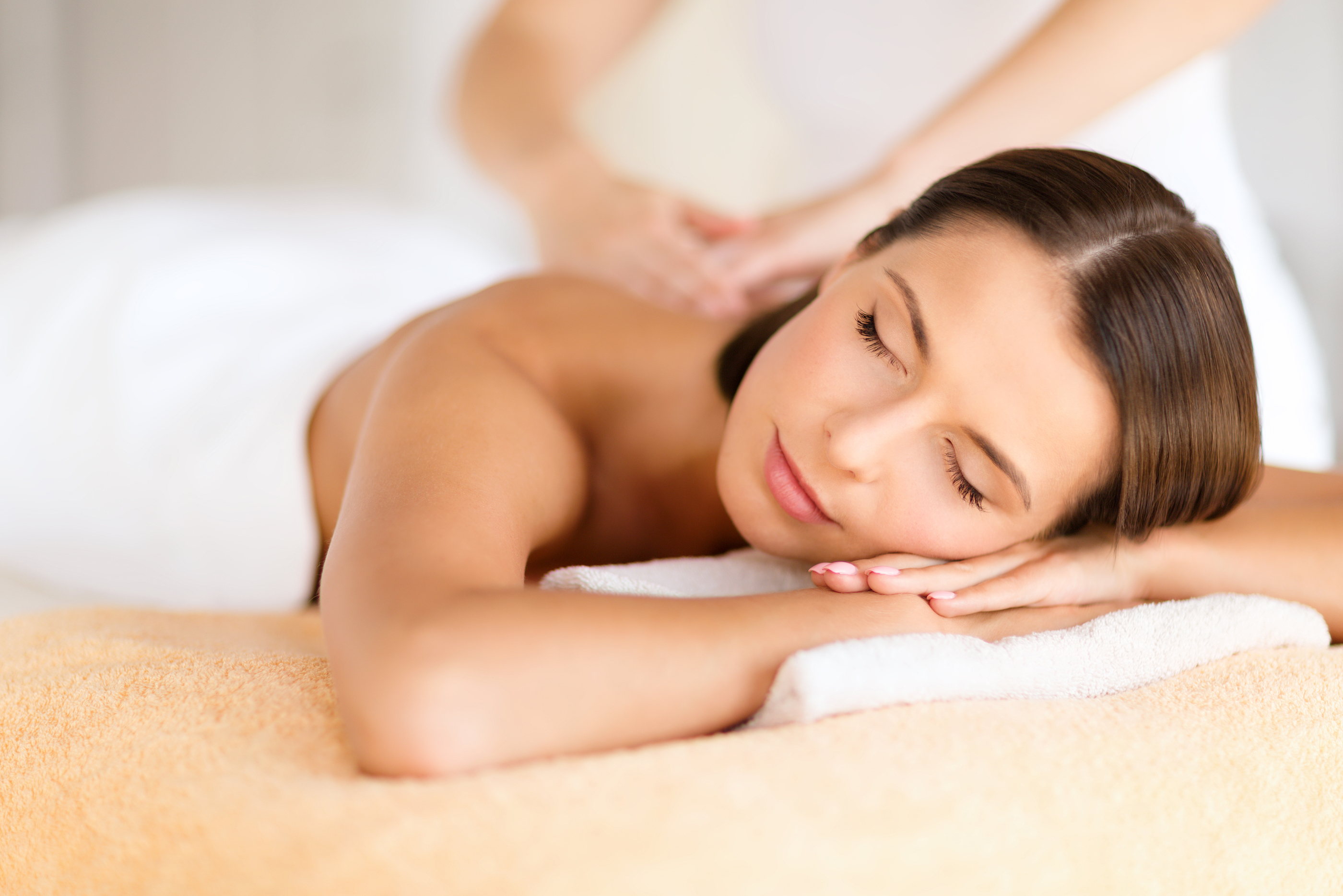 health, beauty, resort and relaxation concept - beautiful woman with closed eyes in spa salon gettin