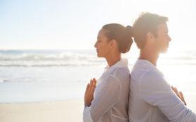 Paare, die auf dem Strand meditieren