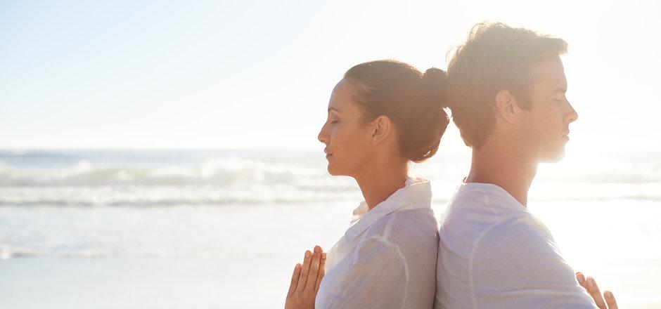 Par mediterar på stranden