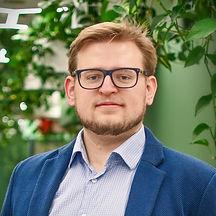 Photo of Jakub Stelmachowski against a green leafy backdrop.