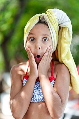 Jeune fille mimant la peur ou stupéfaction au bord d'une piscine