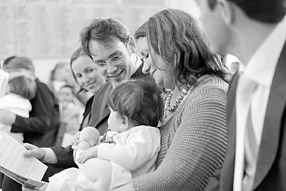 Vue d'une famille sur les bancs de l'église durant un baptême