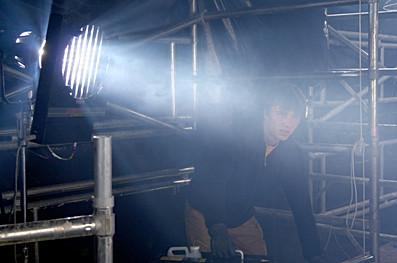 Sous la lumière de son projecteur, l'éclairagiste observe la scène