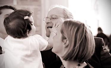Un grand père durant le baptême de sa petite fille