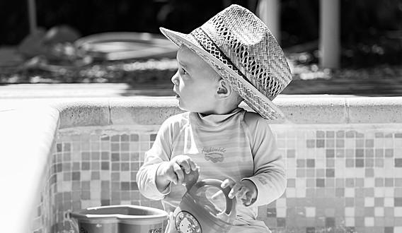 Un enfant au chapeau au jouant au bord de la piscine