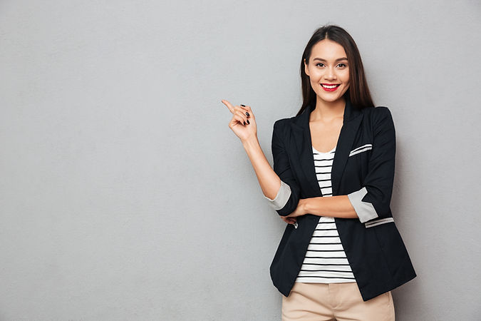 Smiling asian business woman pointing up