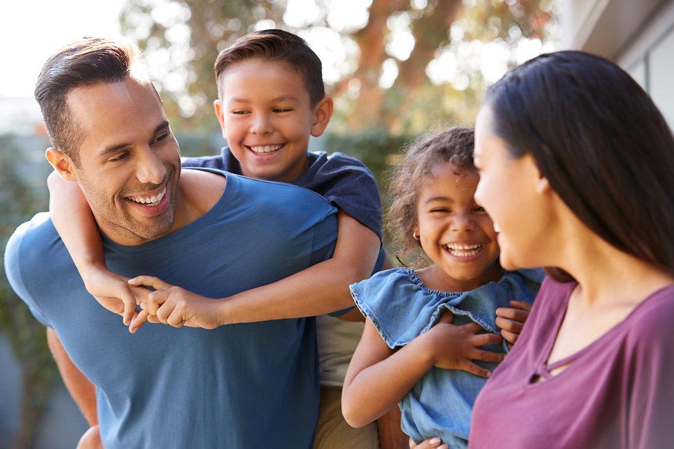 smiling-hispanic-family-with-parents-giv
