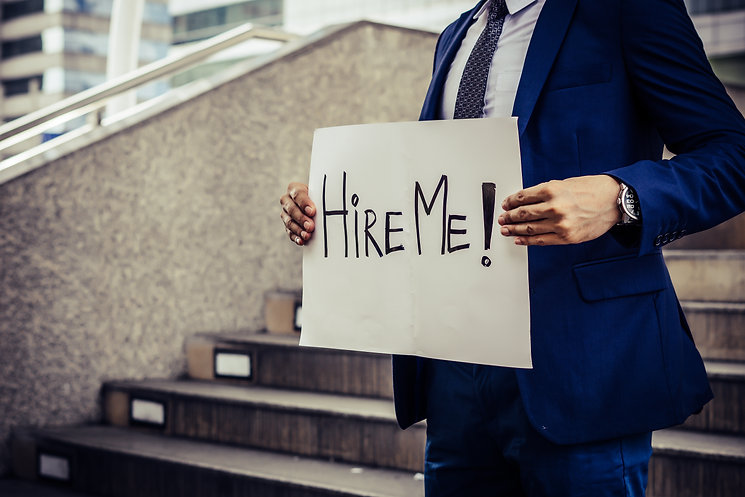 Man in suit holding a hire me sign