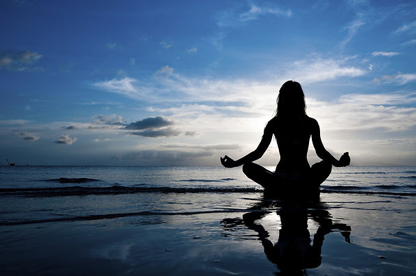 woman on beach at sunrise meditating