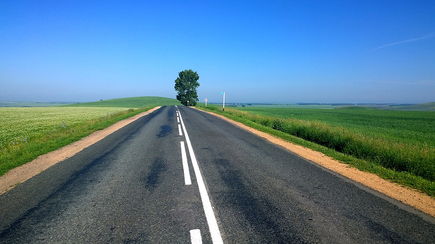 Field on either side of an open road under a blue sky