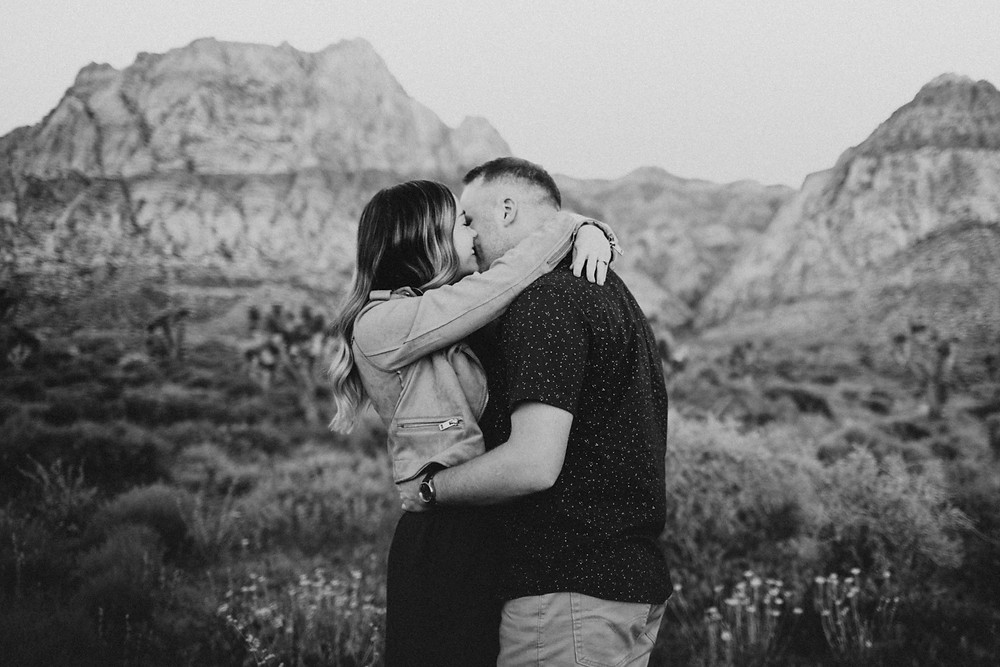 A couple hold each other and laugh together at sunrise in the desert surrounded by cactus and joshua trees. captured by las vegas engagement photographer hayway films