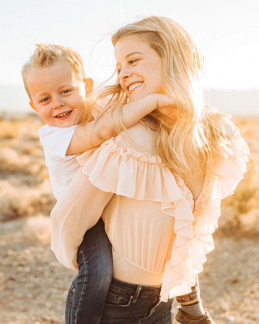 Beautiful mom gives her son a piggy back ride in the desert, Little girl with pigtails in a pink tutu, posing with her brother, captured by las vegas family photographer in tule springs fossil beds