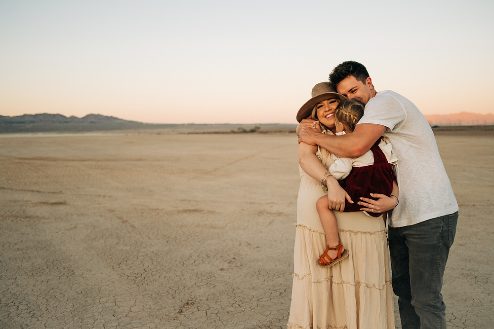 Family of three hugs and laughs for their family portraits at sunset in the dry lake bed outside of las vegas