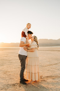 las vegas desert family portraits of mom and dad kissing, while little daughter sits on dads shoulders at sunset