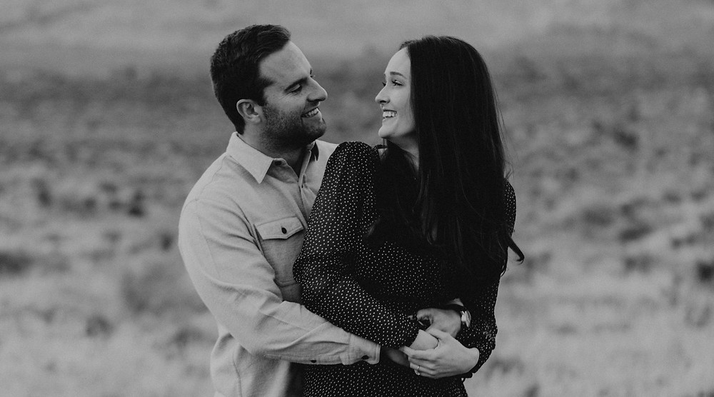Red Rock canyon engagement pictures in the snow. Captured by las vegas wedding photographer hayway films. Black and white photograph of man and woman holding each other and smiling.