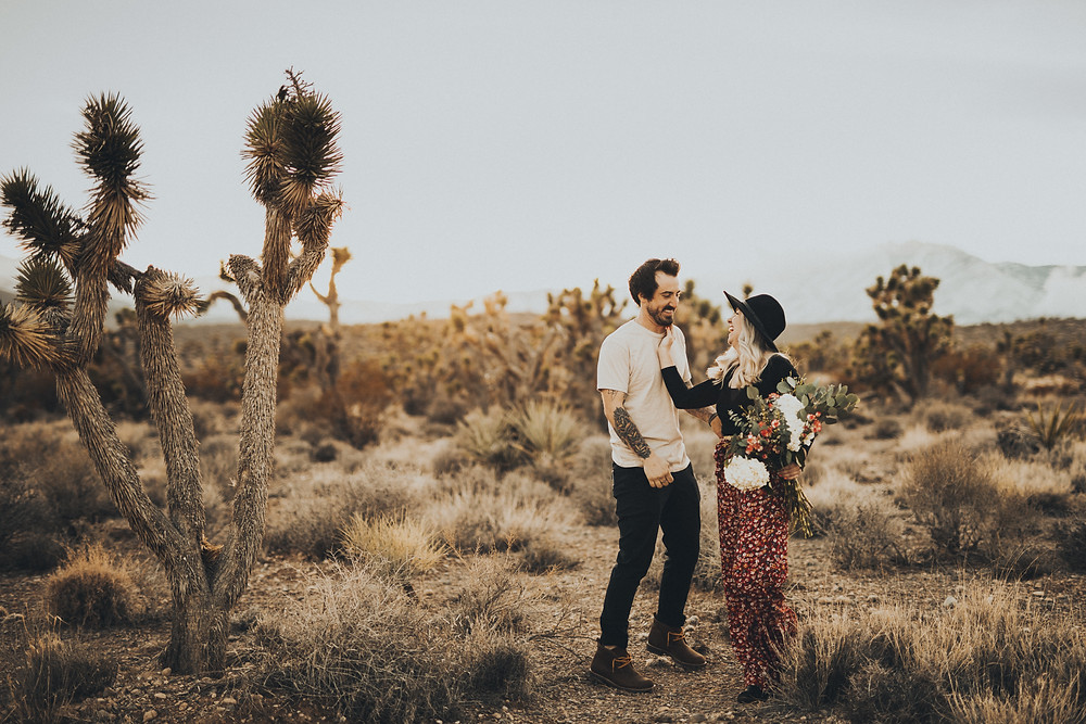 man and woman laughing in the desert Man gives woman a piggyback ride in the desert surrounded by joshua trees. The golden desert with snowy mountains captured by las vegas engagement photographer hayway films.