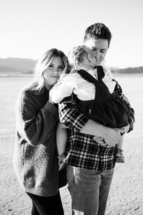 beautiful family of three holds close for family portraits in the desert captured by las vegas family photographer hayway films
