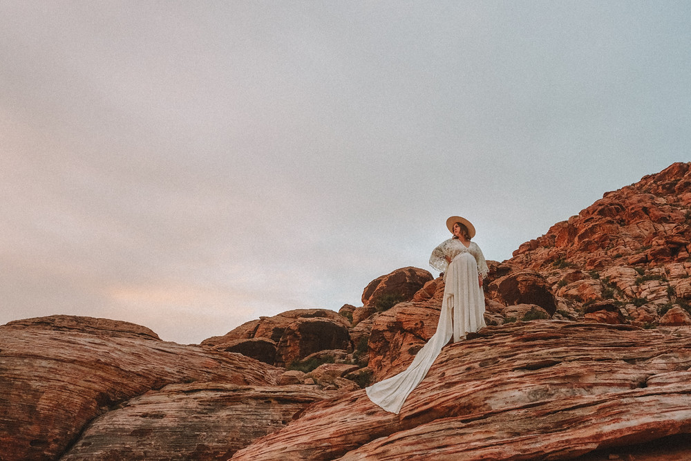 Maternity photos of mom in long white lace boho dress with a white wide brimmed hat, posing on top of red rocks in Valley of fire state park. Captured by las vegas wedding photographer at sunrise