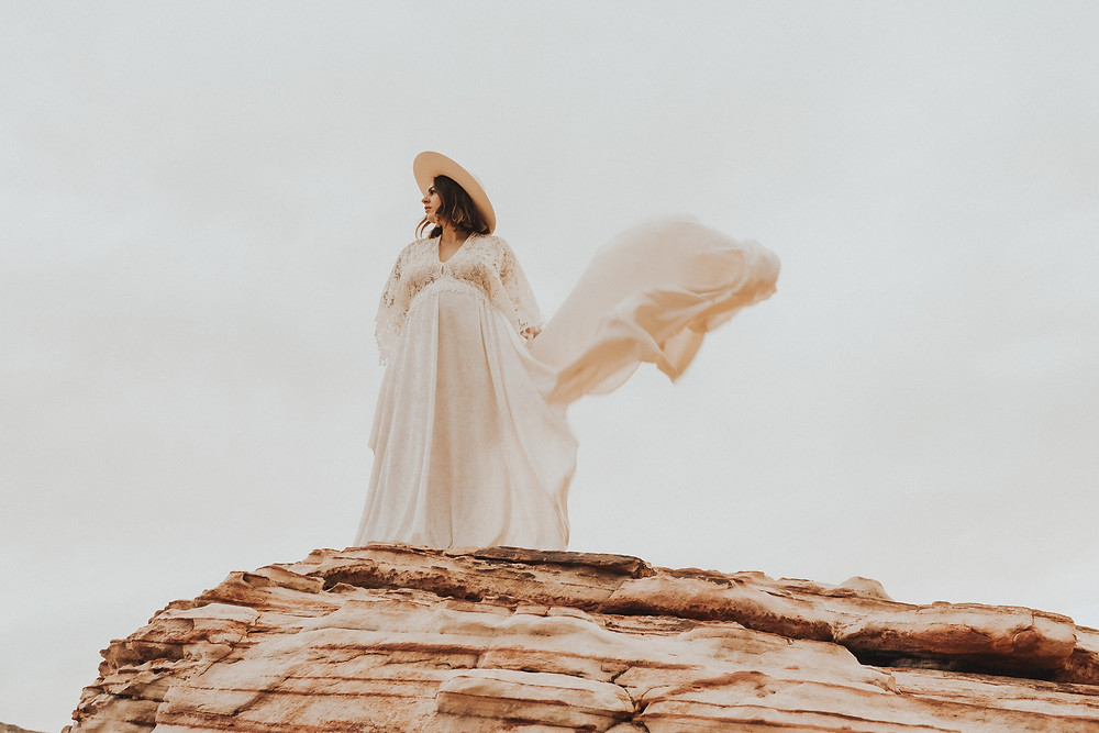 Maternity photos of mom in long white lace boho dress with a white wide brimmed hat, posing on top of red rocks in Valley of fire state park. The long dress flows in the wind. Captured by las vegas wedding photographer at sunrise