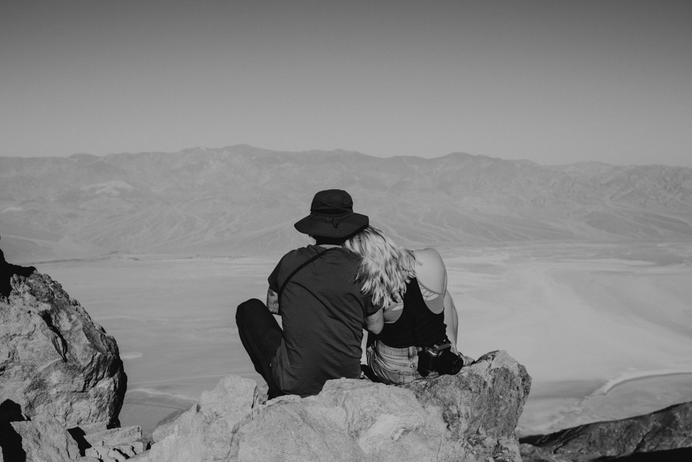 Black and white photograph of a couple sitting and cuddling, backs to the camera, overlooking badwater basin salt flats from dantes view in death valley national park, captured by las vegas elopement photographer hayway films