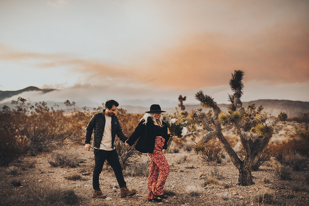 Man and woman hold hands and walk together in the desert at sunset, wit orange sky above them and Man gives woman a piggyback ride in the desert surrounded by joshua trees. The golden desert with snowy mountains captured by las vegas engagement photographer hayway films.