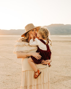 Beautiful sunset portraits of mother and daughter kissing