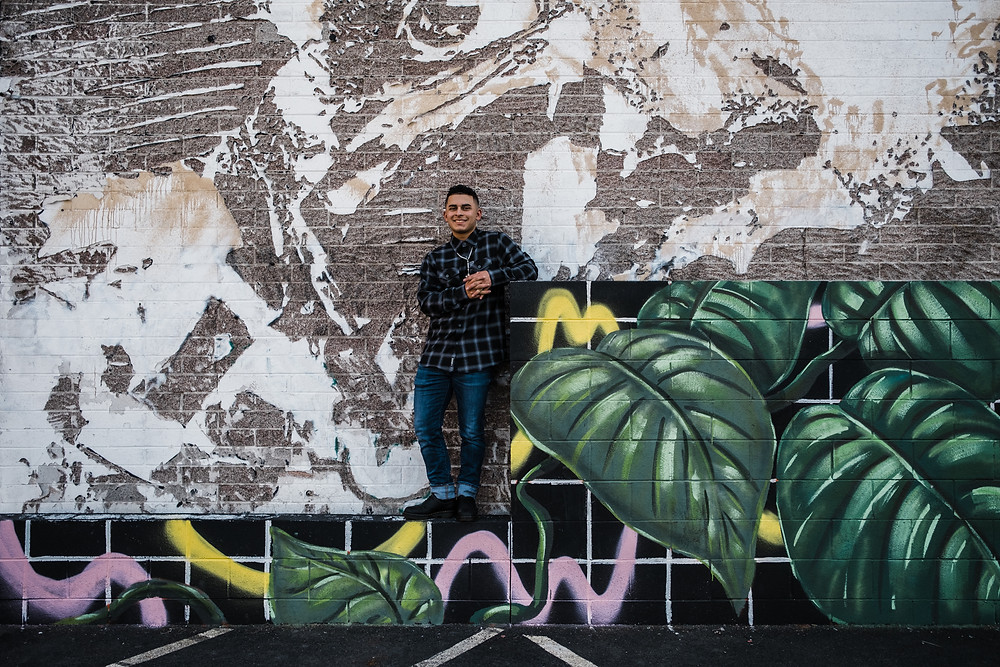 High school senior boy poses for graduation pictures in front of hip mural walls in downtown las vegas. Very cool las vegas senior portrait photographer