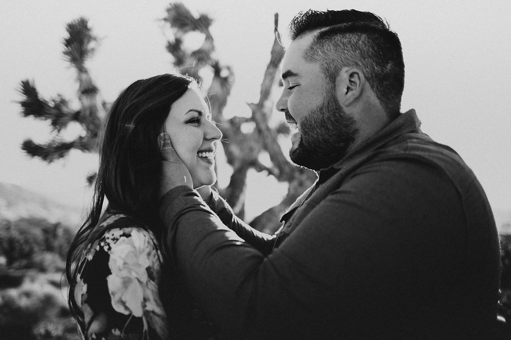 Black and white capture of joyful engagement photos where man holds his wifes face and they laugh captured by las vegas family photographer