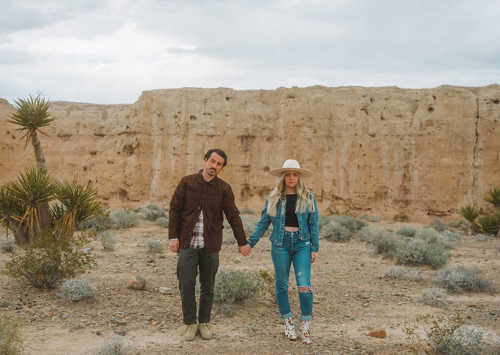 Las Vegas wedding photographers haley and bryen stand together holding hands in the desert on a gloomy day. Woman with blonde hair is wearing a white brimmed hat and denim jacket, while man with brown hair is wearing brown jacket and clarks. They are taking engagement photos in las vegas in front of joshua tree cactus.