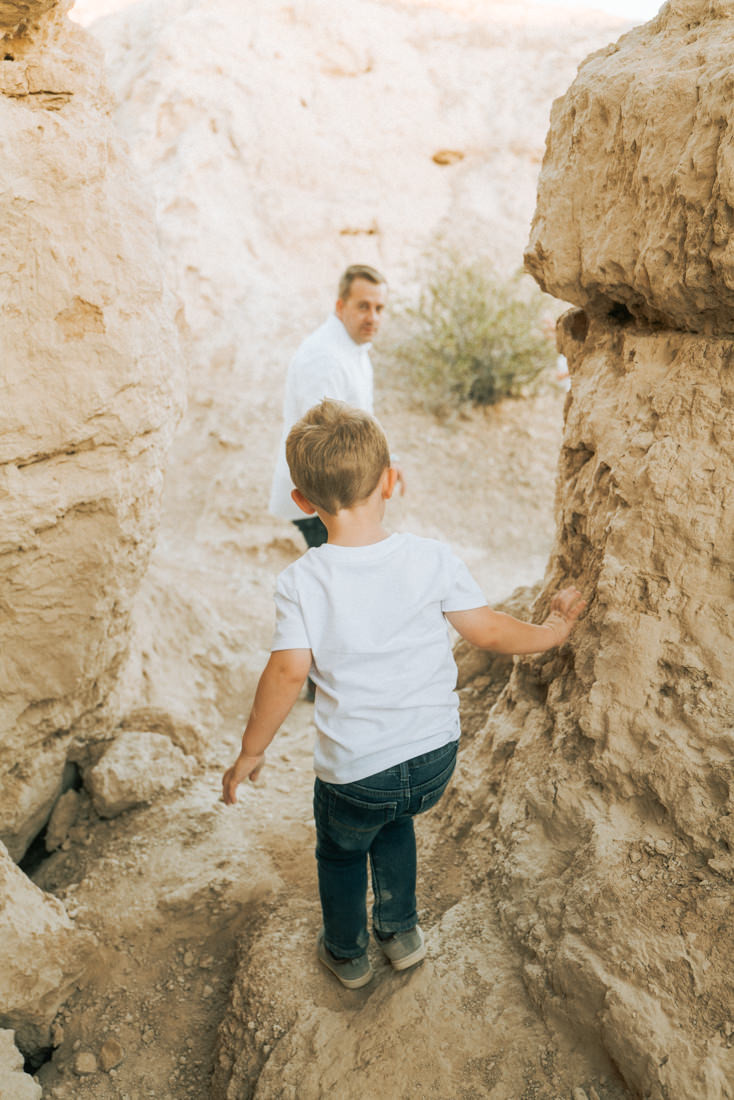 Father and son go on a hike together in the desert, Little girl with pigtails in a pink tutu, posing with her brother, captured by las vegas family photographer in tule springs fossil beds